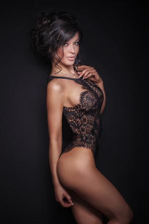 culo donna: Elegante sensuale donna bruna posa in sexy lingerie nera, guardando a porte chiuse. Studio di colpo. Archivio Fotografico