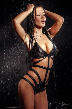 seni: Donna sexy del brunette che propone in biancheria in caso di pioggia. Sfondo nero.