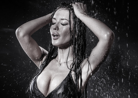 erotic breast: Sexy brunette woman posing in lingerie in rain. Black background.