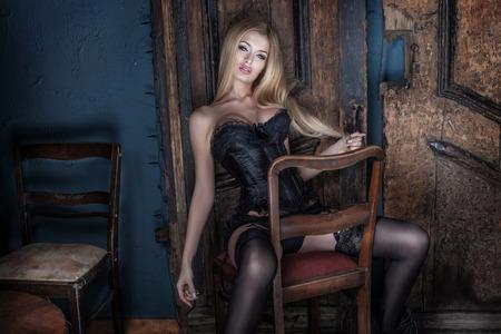 Elegant blonde woman posing in sexy lingerie, looking at camera.