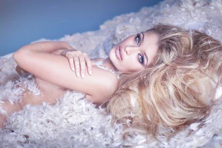 mujer sexy desnuda: Delicada mujer desnuda sensual que miente en plumas. Chica rubia como un ángel.