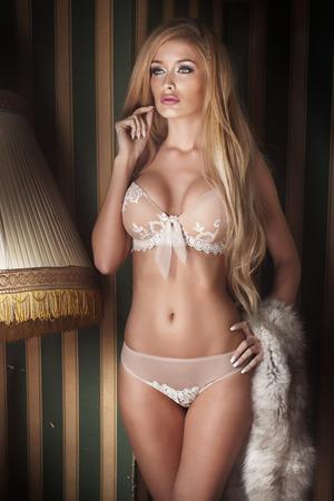 Sensual blonde Dame im eleganten Dessous posiert im Weinleseraum. Standard-Bild - 41521356