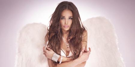 Романтический сексуальная красивая брюнетка ангел позирует в студии.