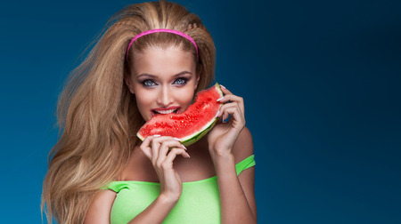 Portrait of sexy beautiful blonde happy woman eating fresh healthy watermelon, looking at camera.
