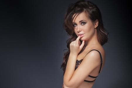 mujer sexy desnuda: Retrato de la belleza de la atractiva delicada mujer morena. Estudio de disparo. Chica con ojos marrones y maquillaje perfecto posando en ropa interior.