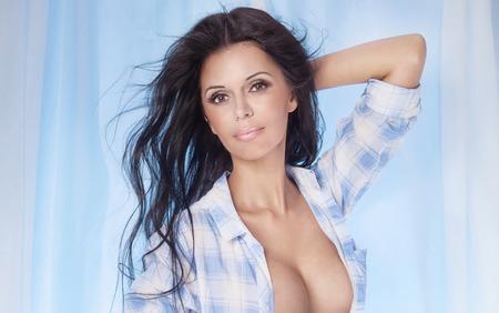 female breast: Portrait of sexy smiling brunette lady. Studio shot.