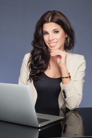 young style: Beautiful brunette businesswoman working, looking at camera and smiling. Attractive woman holding tablet. Elegant style. Studio shot.