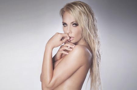 modelos desnudas: Retrato de la belleza de la atractiva mujer rubia delicada. Estudio de disparo. Chica con el pelo mojado largo y el maquillaje perfecto. Chica posando desnuda.