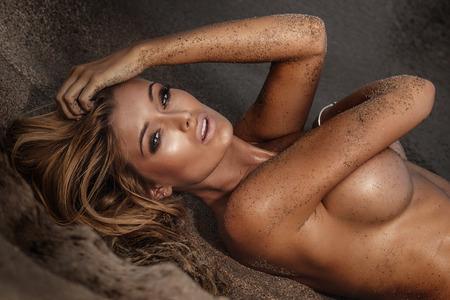topless: Femme blonde sexy couché dans le sable sur la plage, posant nue, regardant la caméra, photo d'été.
