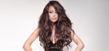 긴 곱슬 머리와 완벽한 메이크업과 관능적 인 아름다운 갈색 머리 여자의 초상화. 스튜디오 촬영.