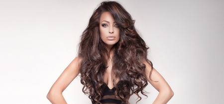 modelo: Retrato de sensual y bella mujer morena con el pelo largo y rizado y maquillaje perfecto. Estudio de disparo.