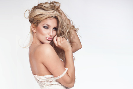 labios sexy: Retrato de la belleza de la atractiva mujer rubia delicada. Estudio de disparo. Chica con el pelo largo y rizado y maquillaje perfecto. Foto de archivo