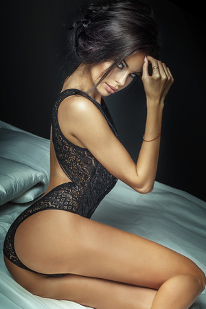 chica sexy: Señora atractiva morena muy posando en ropa interior negro, sentado en la cama. Mujer caliente con la carrocería delgada perfecta. Chica mirando a la cámara. Foto de archivo