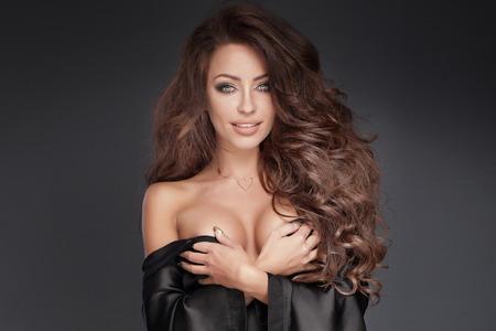 mujeres jovenes desnudas: Retrato de sensual y bella mujer morena con el pelo largo y rizado y maquillaje perfecto. Niña sonriente. Estudio de disparo.