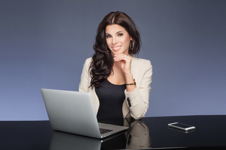 secretary desk: Beautiful brunette businesswoman working, looking at camera and smiling. Attractive woman holding tablet. Elegant style. Studio shot.