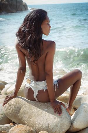 modelos desnudas: Atractiva mujer afroamericana atractiva que se relaja en la playa. Estilo de verano.
