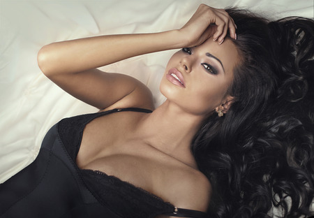 Close-up schoonheid portret van sexy brunette vrouw met grote bruine ogen, perfecte make-up en lang haar. Meisje liggend in bed, ontspannen. Stockfoto