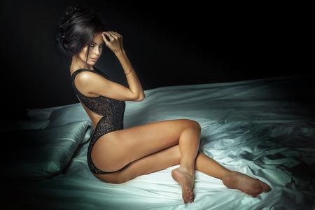 piernas sexys: Señora atractiva morena muy posando en ropa interior negro, sentado en la cama. Mujer caliente con la carrocería delgada perfecta. Chica mirando a la cámara. Foto de archivo