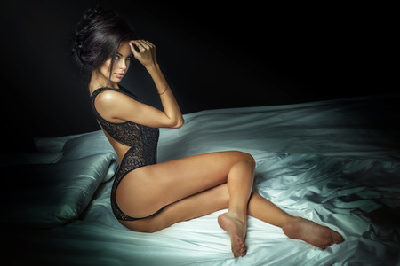 fashion girl style: Very sexy brunette lady posing in black lingerie, sitting on bed. Hot woman with perfect slim body. Girl looking at camera.