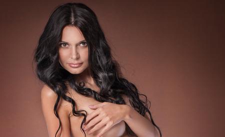 mujer sexy desnuda: Retrato de mujer desnuda sexy con grandes ojos marrones y cabello largo y rizado. Estudio de disparo.