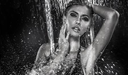 Mujer hermosa atractiva posando húmedo sobre las gotas de agua. Estudio de disparo.