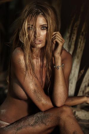desnudo: Mujer atractiva rubia sentada en la playa, posando desnuda, mirando a cámara, foto de Verano.