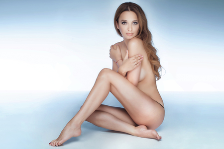 Full photo of naked beautiful woman with perfect slim body. Girl sitting, looking at camera. Studio shot.
