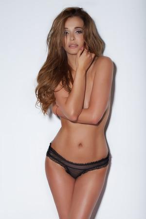 mujeres jovenes desnudas: Mujer hermosa atractiva con la carrocería delgada perfecta posando en el estudio, el uso de ropa interior sensual negro, mirando a la cámara.