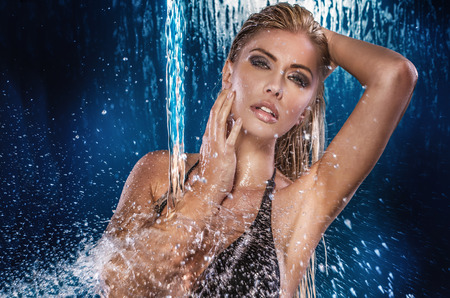 long blonde hair: Sexy beautiful woman posing wet over water drops. Studio shot.