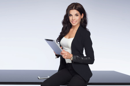 Beautiful brunette businesswoman working, looking at camera and smiling. Attractive woman holding tablet. Elegant style. Studio shot.