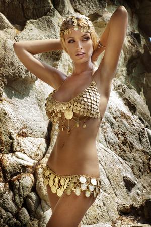 mujer rubia desnuda: Mujer atractiva con la carrocería delgada perfecta posando en traje de moda sobre las rocas. Vista tropical.