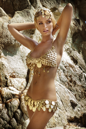 nude: Sexy woman with perfect slim body posing in fashionable costume over rocks. Tropical view.