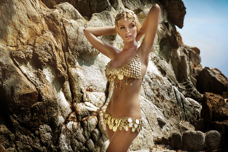 naked blonde: Sexy woman with perfect slim body posing in fashionable costume over rocks. Tropical view.