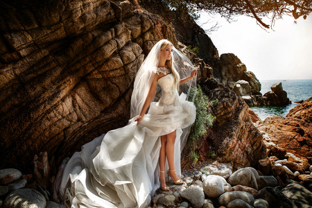cliffs: Beautiful gorgeous blonde bride posing in fashionable wedding dress outddor. Coastal view. Spain.