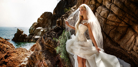 Beautiful gorgeous blonde bride posing in fashionable wedding dress outddor. Coastal view. Stock Photo