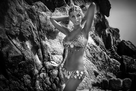nude young woman: Sexy woman with perfect slim body posing in fashionable costume over rocks. Tropical view.