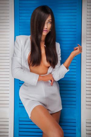 mujer desnuda: Elegante atractiva hermosa dama Morena con largo cabello sano posando, mirando a la cámara. Mujer sensual con el pecho desnudo. Estudio de disparo.