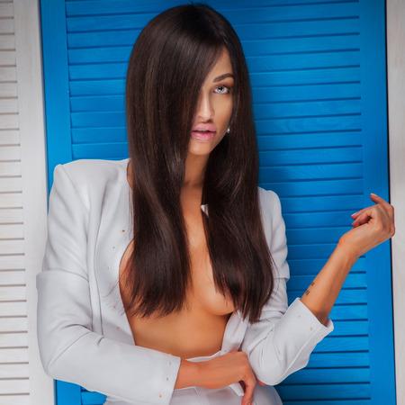 mujer sexy desnuda: Elegante atractiva hermosa dama Morena con largo cabello sano posando, mirando a la cámara. Mujer sensual con el pecho desnudo. Estudio de disparo.