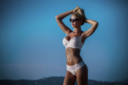 Summer photo of beautiful sexy blonde woman in elegant lace lingerie. Sunny day. Luxury resort. Girl wearing fashionable sunglasses. Stock Photo
