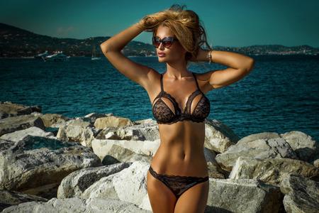 Zomer foto van mooie sexy blonde vrouw in elegante kant lingerie. Zonnige dag. Luxe resort. Meisje met perfect slank lichaam. Stockfoto