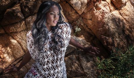 mannequin africain: Sexy femme afro-américaine en plein air posant. Fille aux longs cheveux bouclés, en regardant ailleurs.