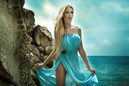 dresses: Beautiful blonde woman walking on the beach, wearing fashionable blue dress. Sexy look. Summer photo.