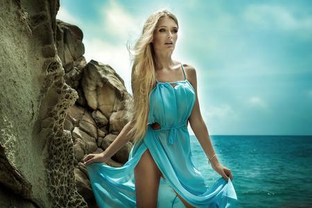 rubia: Hermosa mujer rubia caminando por la playa, con un vestido azul de moda. Mirada atractiva. Foto del verano.
