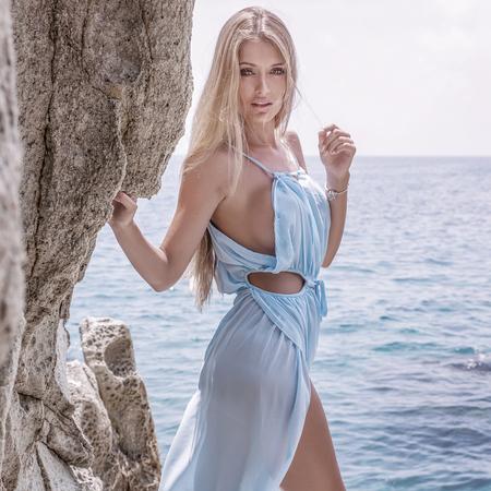 sexy dress: Beautiful blonde woman walking on the beach, wearing fashionable blue dress. Sexy look. Summer photo.