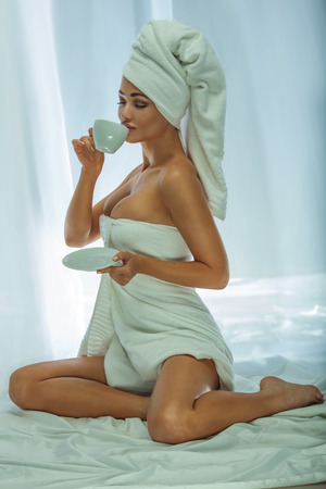 nude woman sitting: Beautiful attractive woman drinking coffee. Girl with white towel on head. Morning photo.