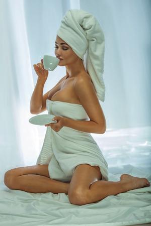 mujer desnuda sentada: Hermosa atractiva mujer beber caf�. Chica con una toalla blanca en la cabeza. Photo Ma�ana.