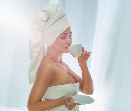 nude young: Красивая привлекательная женщина пить кофе. Девушка с белым полотенцем на голове. Утро фото.