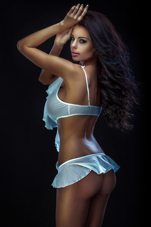 Sexy beautiful brunette lady with long curly hair looking at camera, wearing delicate lingerie. Studio shot. photo