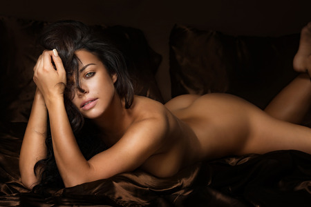 naked: Beautiful sexy brunette woman lying naked, looking at camera. Girl with perfect body.