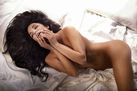 nice breast: Sexy naked woman lying in bed, relaxing. Brunette sensual lady.